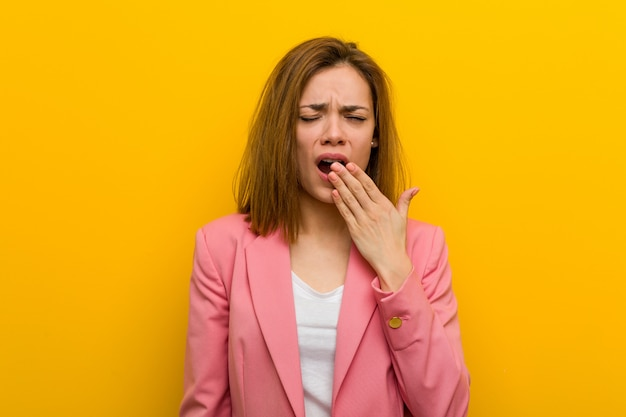 Young fashion business woman yawning showing a tired gesture covering mouth with her hand.