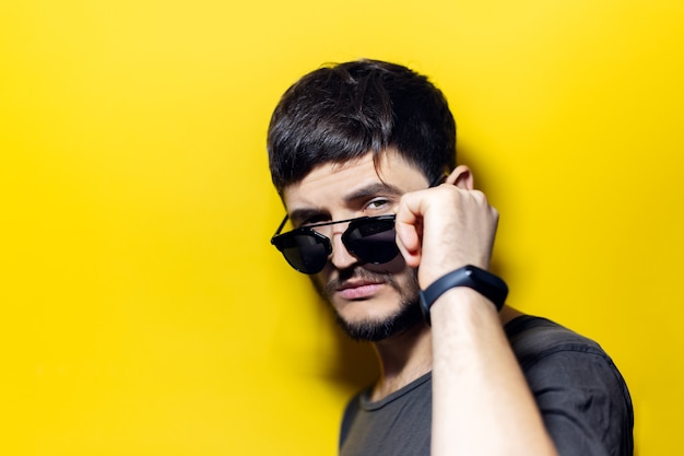 Young fashion confident man, taking off sunglasses, wearing smartwatch on yellow wall.
