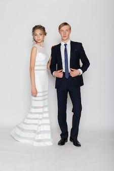 スタジオで灰色の表面に若いファッションカップル