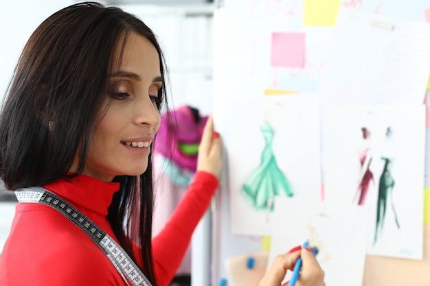 若いファッションデザイナーが紙に新しい服のコレクションを作成