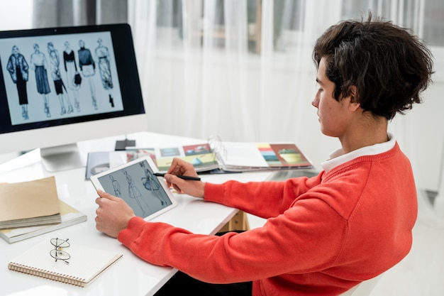 Молодой модельер просматривает новые модели на сенсорной панели, сидя за столом перед экраном компьютера