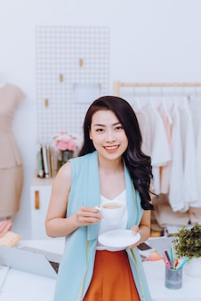 Молодой модельер в своем ателье делает паузу и пьет кофе