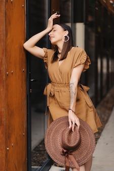 Wideの広い帽子と夏のドレスに身を包んだ若者のファッションの女の子が歩くし、旧市街でポーズ