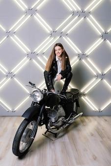 Молодая модная девушка позирует в черной коже с мотоциклом.