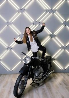 Молодая модная девушка позирует в черной коже с мотоциклом. Premium Фотографии