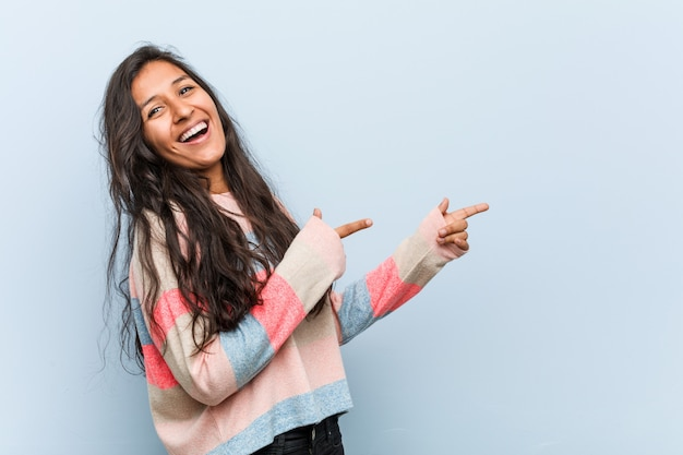Young fashion indian woman excited pointing with forefingers away.
