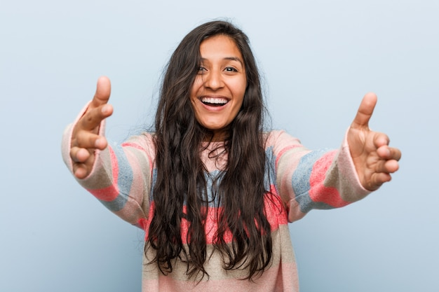 Young fashion indian woman feels confident giving a hug