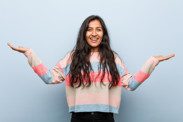 Young fashion indian woman makes scale with arms, feels happy and confident.