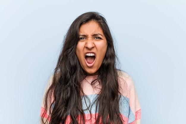非常に怒っていると積極的な叫びの若者のファッションインドの女性。