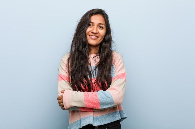 自信を持って、決意を持って腕を組んでいる若いファッションインド人女性。