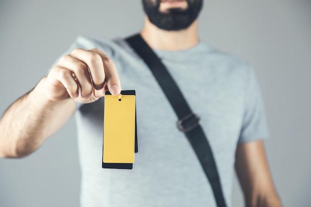 黄色のタグを持っている若いファッション男の手