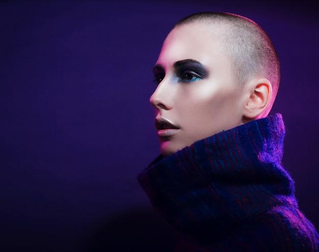 スタジオでポーズをとる若いファッションモデル。ハゲ。明るいメイク。ピンクの背景の上。