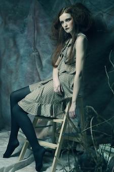 드라마 장식의 자에 앉아 젊은 패션 모델