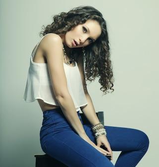 Молодая фотомодель, сидящая на стуле, студийный снимок