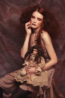 창의적인 메이크업으로 드라마 장식의 자에 앉아 젊은 패션 모델 여자