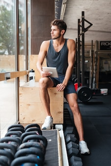 Young fashion sportsman with tablet. against the backdrop of weights