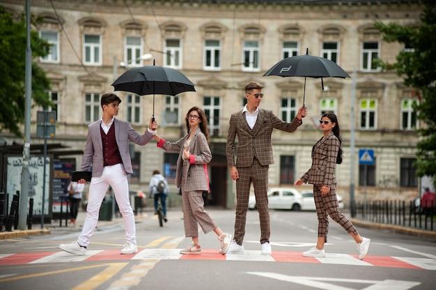 雨の通りを歩く若いファッションの女性と男性