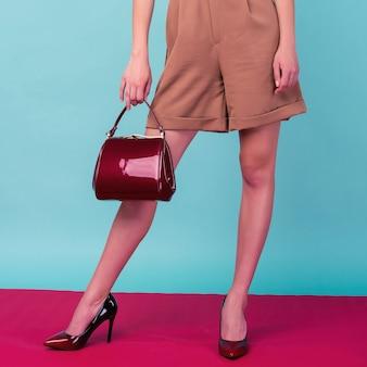 若いファッションの女性は青い背景で隔離のハンドバッグクラッチを保持します-画像