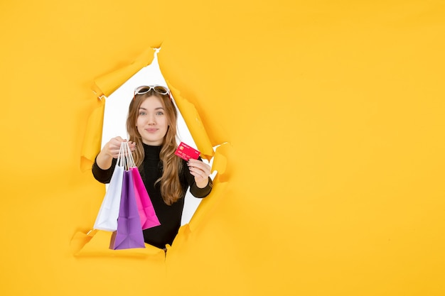 Молодая модная женщина, держащая хозяйственные сумки и кредитную карту через рваную бумажную дыру в стене