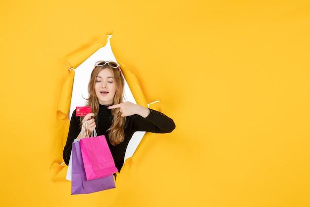 壁の破れた紙の穴を通して買い物袋とクレジットカードを保持している若いファッション女性