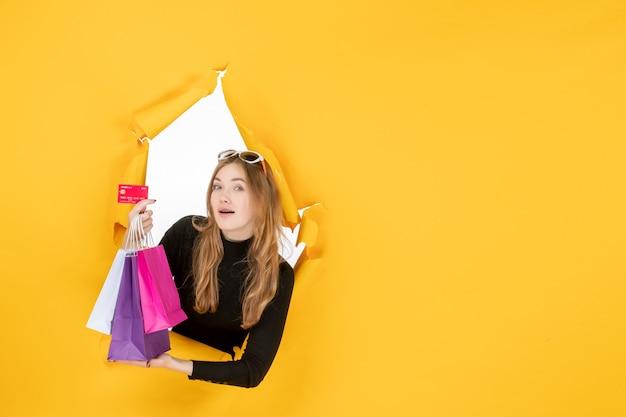 벽에 찢어진 종이 구멍을 통해 쇼핑백과 신용 카드를 들고 젊은 패션 여자