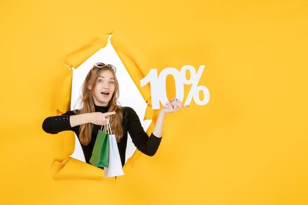 벽에 찢어진 종이 구멍을 통해 쇼핑백과 할인 비율을 들고 젊은 패션 여자 무료 사진
