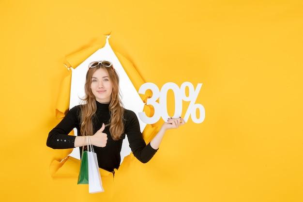 벽에 찢어진 종이 구멍을 통해 쇼핑백과 할인 비율을 들고 젊은 패션 여자