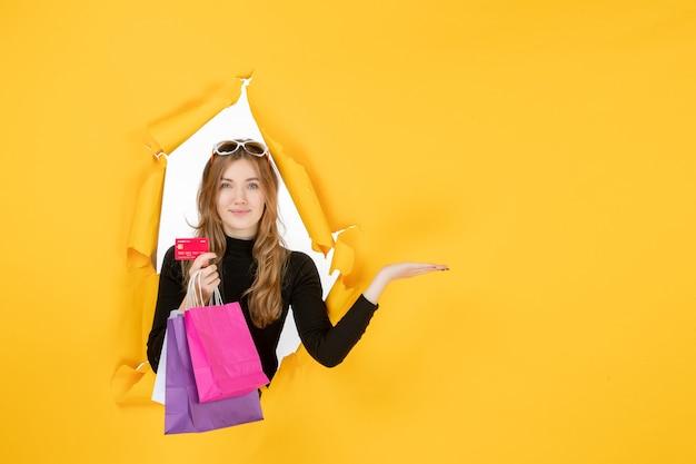 Giovane donna alla moda che tiene in mano le borse della spesa e la carta di credito attraverso il foro di carta strappata nel muro