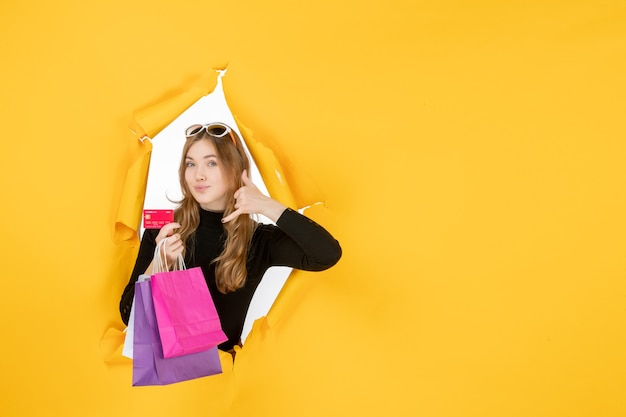 Young fashion woman holding shopping bags and credit card through torn paper hole in the wall