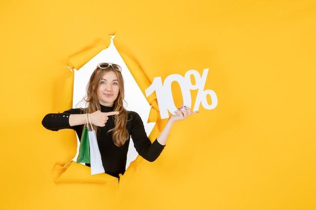 Giovane donna alla moda che tiene in mano le borse della spesa e la percentuale di sconto attraverso il foro di carta strappata nel muro