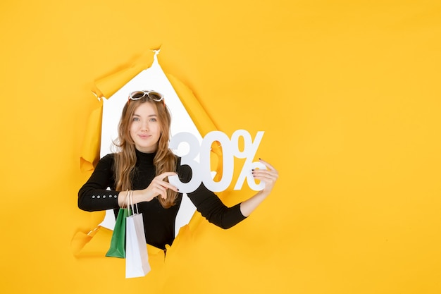 Young fashion woman holding shopping bags and discount percentage through torn paper hole in the wall