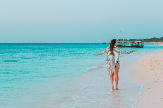 Молодая женщина моды в зеленом платье на пляже