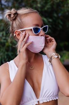 자연 속에서 흰색 자르기 가기, 선글라스와 흰색 의료 얼굴 마스크에 젊은 패션 여자