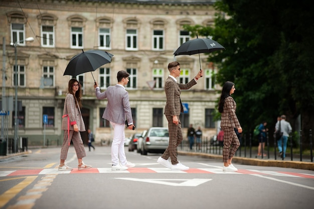 Young fashion woman and man walking on the rainy street