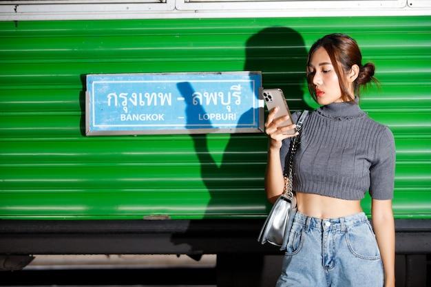 젊은 패션 여자 모델은 여름철 기차역에서 세련되고 시원합니다. 개념은 covid 후 여행 준비