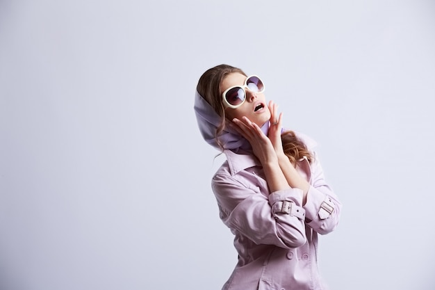 Young fashion woman posing in studio wearing pink coat and white sunglasses