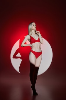 Young fashion woman in red lingerie underwear swimsuit light and shadow, sensitive woman posing in a circle of light