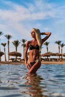 ビーチで水に立っている若いファッションの女性