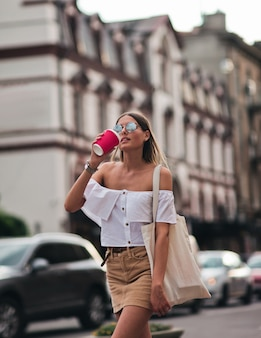 Young fashion woman in trendy summer clothes holding coffee cup while walking around the city