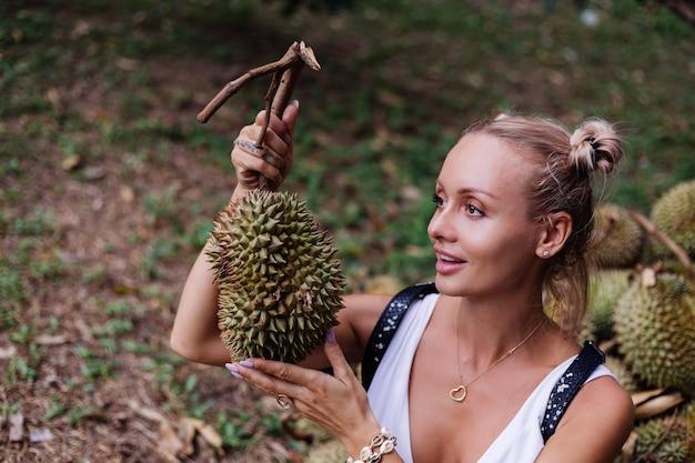 Moda giovane donna su un campo tropicale con frutti durian