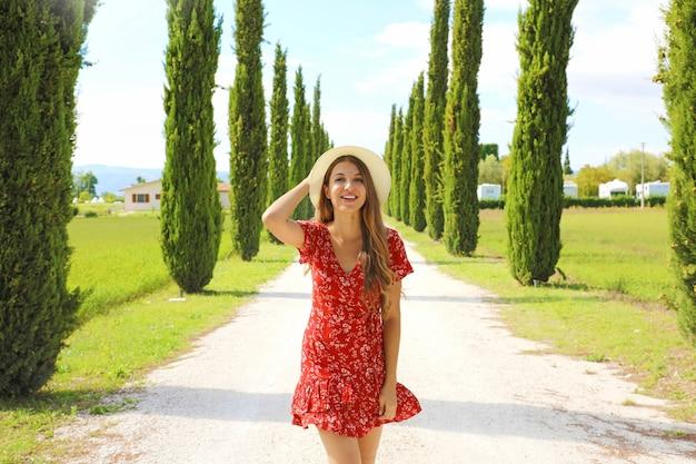 晴れた日にヒノキのレーンを歩く若者のファッション女性