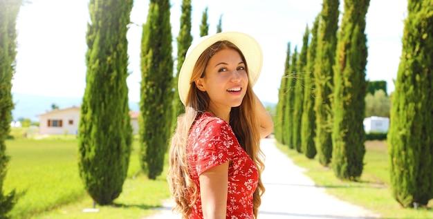 糸杉の車線を歩く若者のファッション女性