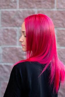 レンガの背景にピンクの髪のスタイルを持つ若者のファッション女性