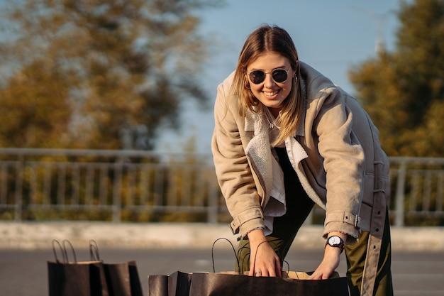 Молодая модная женщина с хозяйственными сумками на парковке