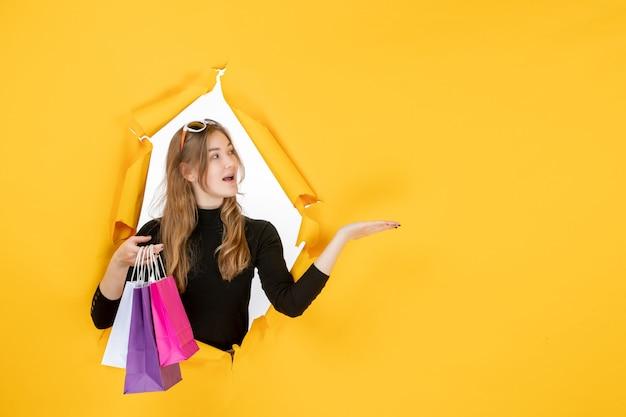 Молодая модная женщина с хозяйственными сумками через рваную бумажную дыру в стене