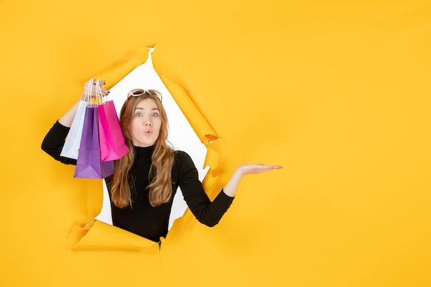 Giovane donna alla moda con borse della spesa attraverso il buco della carta strappata nel muro