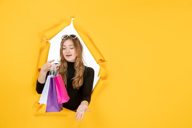 Young fashion woman with shopping bags through torn paper hole in the wall
