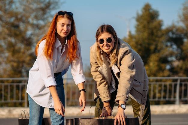 Молодые модные женщины с хозяйственными сумками на парковке