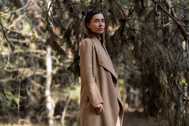 베이지색 코트를 입은 젊고 세련되고 아름다운 소녀가 차나 커피를 가져가 숲 속에 혼자 서 있다