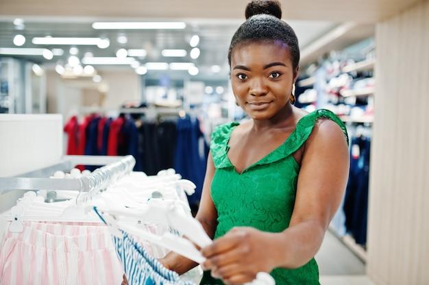 緑のコンビドレス衣料品店でのショッピングでファッショナブルでセクシーなアフロの若い女性。ナイトウェアとランジェリーのセクター。